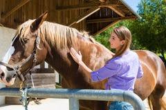 Ung kvinna i stall med hästen Royaltyfri Fotografi