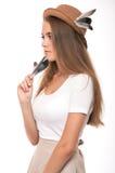 Ung kvinna i sugrörhatt med fjädrar Blont flickastudioskott Royaltyfria Bilder