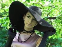 Ung kvinna i svart hatt Arkivfoto