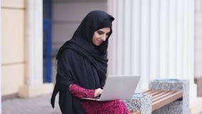 Ung kvinna, i svart hijabsammanträde i gatan och sökande för något i internet Stående av att le barn stock video