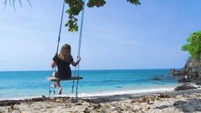 Ung kvinna i svart klänning som påskyndar på strandgunga på blått havslandskap Lycklig kvinna som kopplar av på gunga på sommarst arkivfilmer