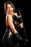 Ung kvinna i svart klänning under en konsert Fotografering för Bildbyråer
