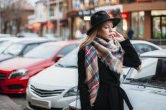 Ung kvinna i svart lag, hatt och halsduk flicka som går runt om stad arkivbild