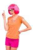 Ung kvinna i svarta exponeringsglas och rosa peruk som pekar upp. Royaltyfri Foto