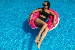 Ung kvinna i swimwear- och solglasögonlögner på den ljusa uppblåsbara cirkeln arkivfoto