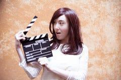 Ung kvinna i 70-talhippiestil som ler med clapperboard Royaltyfria Foton