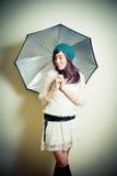 Ung kvinna i 70-talhippiestil som poserar att se ner med umbrell Royaltyfri Foto