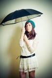 Ung kvinna i 70-talhippiestil som poserar med paraplyet Arkivbilder