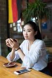 Ung kvinna i telefonen på kafét Royaltyfri Bild