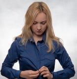 Ung kvinna i tillfällig blå skjorta som klär upp och ner ser arkivbild