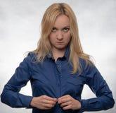 Ung kvinna i tillfällig blå skjorta som klär upp och ser rak in i kamera royaltyfri bild
