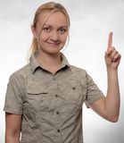 Ung kvinna i trekking skjorta som pekar upp arkivbild