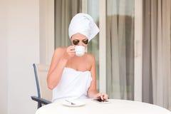 Ung kvinna i under-öga lappar som skriver smsmeddelandet och dricker kaffe på hotellterrasssemesterorten r arkivfoton
