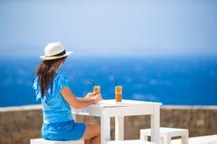 Ung kvinna i utomhus- kafé som dricker kallt kaffe som tycker om havssikt Arkivbild