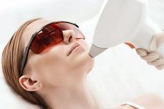 Ung kvinna i uv skyddande exponeringsglas som mottar laser-hudomsorg på framsida arkivbild