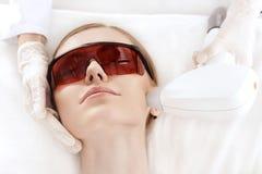 Ung kvinna i uv skyddande exponeringsglas som mottar laser-hudomsorg på framsida arkivbilder