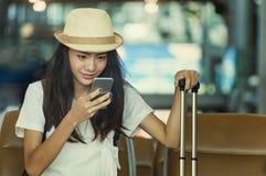 Ung kvinna i väntande på flygresa för flygplats genom att använda den smarta telefonen fotografering för bildbyråer