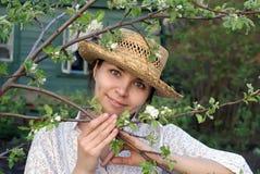 Ung kvinna i vårträdgård royaltyfria bilder