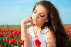 ung kvinna i vallmofält Arkivbilder
