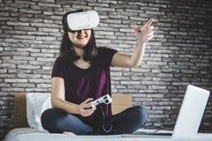 Ung kvinna i virtuell verklighethörlurar med mikrofon eller exponeringsglas som 3d spelar vid Royaltyfria Bilder