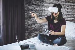 Ung kvinna i virtuell verklighethörlurar med mikrofon eller exponeringsglas som 3d spelar vid fotografering för bildbyråer