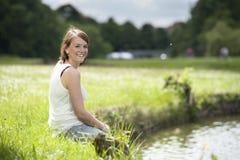 Ung kvinna i vit som placeras på sjön fotografering för bildbyråer