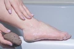 Ung kvinna, kroppomsorg, kvinna som har hennes fot att skuras av borsten arkivfoton