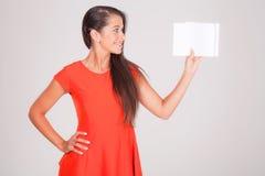 Ung kvinna, leenden på anteckningsboken Arkivfoton
