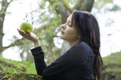 Ung kvinna med äpplet mot bakgrund field blåa oklarheter för grön vitt wispy natursky för gräs Arkivfoto