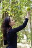 Ung kvinna med äpplet mot bakgrund field blåa oklarheter för grön vitt wispy natursky för gräs Arkivbilder