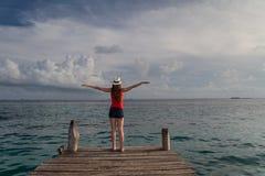 Ung kvinna med öppna armar som tycker om solnedgången på havet Fotografering för Bildbyråer