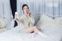 Ung kvinna med andframsidan som tar modern selfie i rummet Fotografering för Bildbyråer