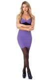 Ung kvinna med armar som bär åtsittande purpurfärgade korta Mini Dress och för hög häl skor arkivfoto