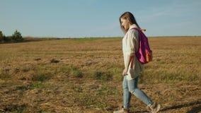 Ung kvinna med att gå för rosa färgryggsäck arkivfilmer