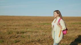 Ung kvinna med att gå för rosa färgryggsäck stock video