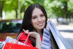 Ung kvinna med att gå för shoppingpåsar Royaltyfria Bilder