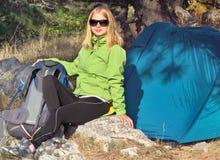 Ung kvinna med att le framsidafotvandraresammanträde med att campa för ryggsäck som och för tält är utomhus- Arkivfoton