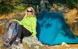 Ung kvinna med att le framsidafotvandraresammanträde med att campa för ryggsäck som och för tält är utomhus- Fotografering för Bildbyråer
