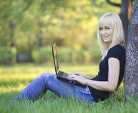 Ung kvinna med bärbar dator royaltyfri foto