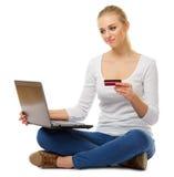 Ung kvinna med bärbar dator- och plast-kortet arkivbild