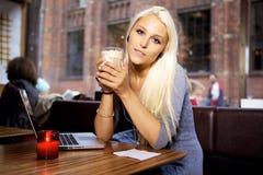 Ung kvinna med bärbar dator på cafen Arkivfoto