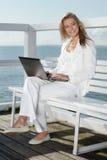 Ung kvinna med bärbara datorn Arkivbild