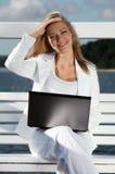 Ung kvinna med bärbara datorn Fotografering för Bildbyråer
