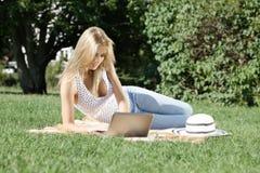 Ung kvinna med bärbara datorn Arkivbilder