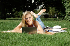 Ung kvinna med bärbara datorn Arkivfoto