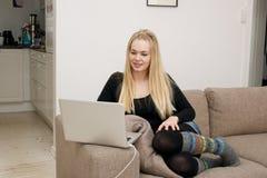 Ung kvinna med bärbara datorn Royaltyfria Foton