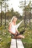 Ung kvinna med bärbara datorn i natur Royaltyfri Bild