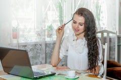 Ung kvinna med bärbara datorn och översikten arkivfoto