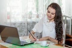 Ung kvinna med bärbara datorn och översikten royaltyfri bild