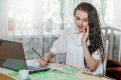 Ung kvinna med bärbara datorn och översikten arkivbild
